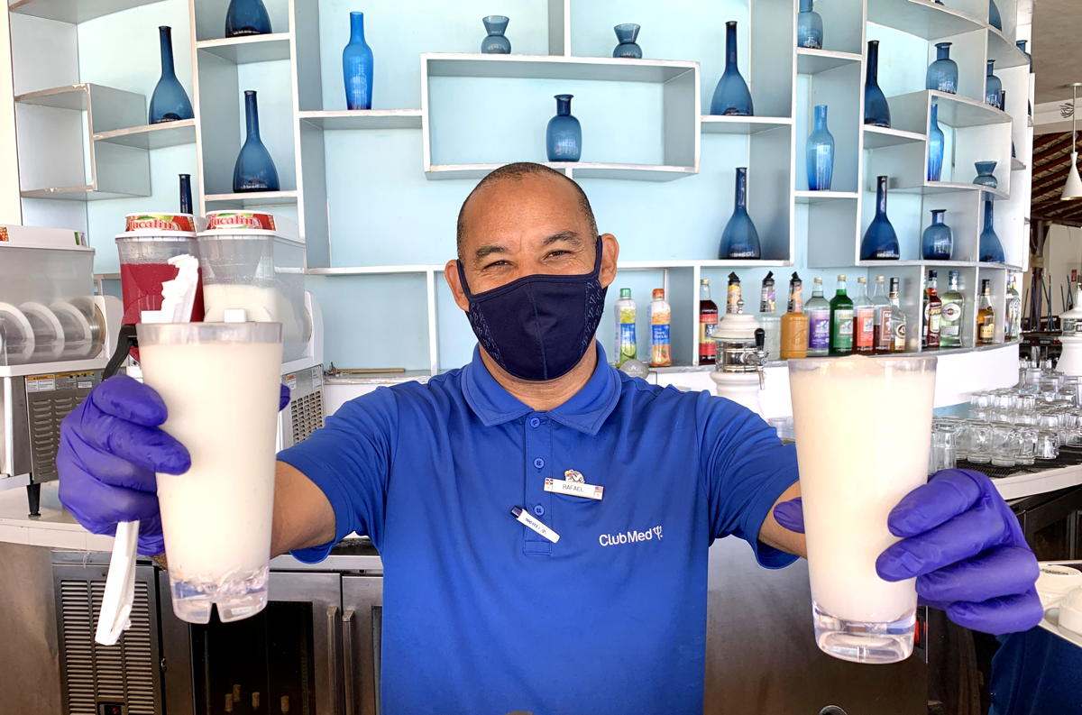 A masked bartender serves drinks at the Indigo beach bar at Club Med Punta Cana.