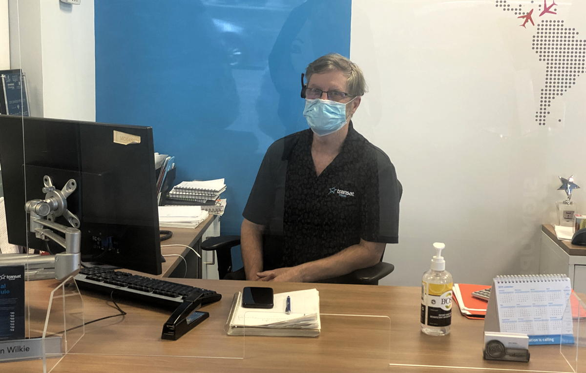 A masked travel advisor greets customers behind Plexiglass in Ontario. (Supplied)
