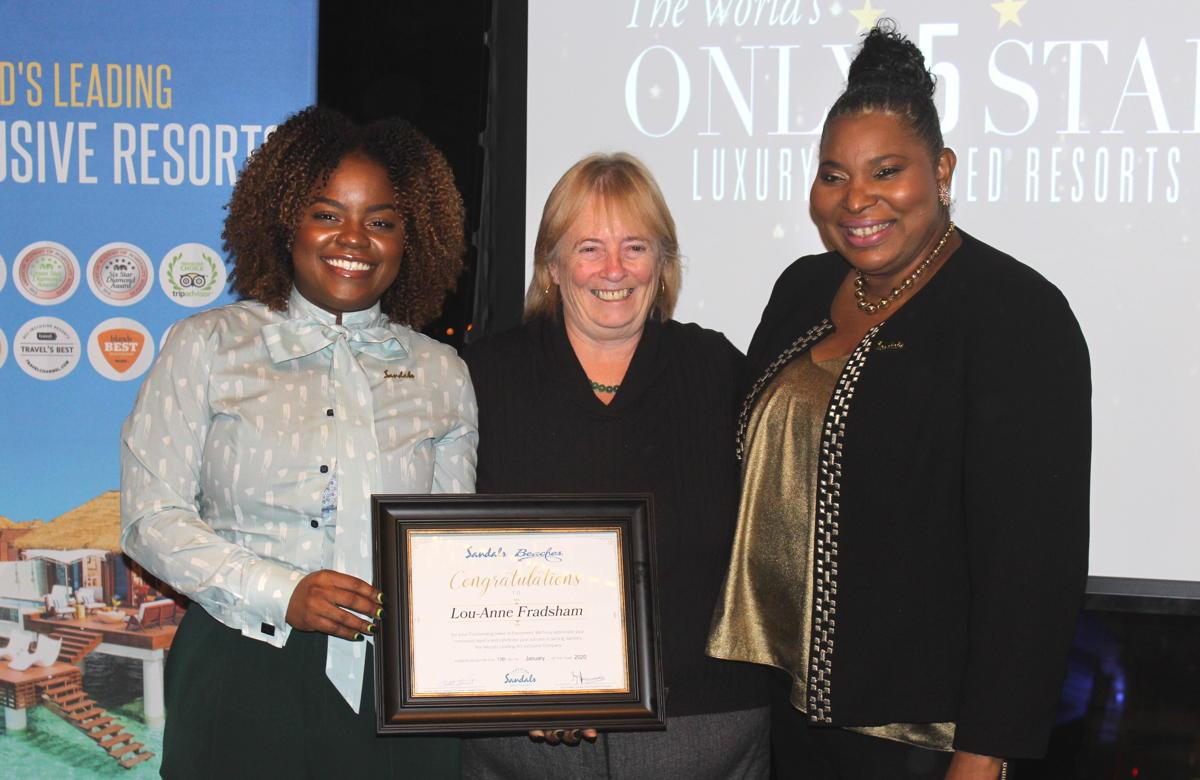 Giselle Williams (left) & Maureen Barnes-Smith (right) present travel advisor Lou-Anne Fradsham (centre) the Outstanding Sales Achievement award.