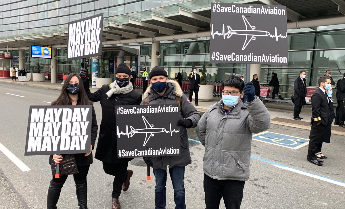 Protesters carry signs at the March to Save Canadian Aviation at YYZ on Oct. 30.