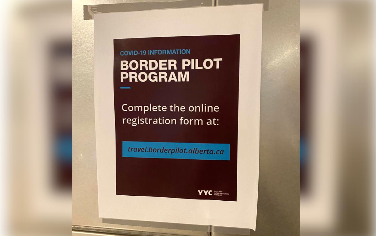 A sign at YYC encourages travellers to register for the pilot project online. (Supplied)