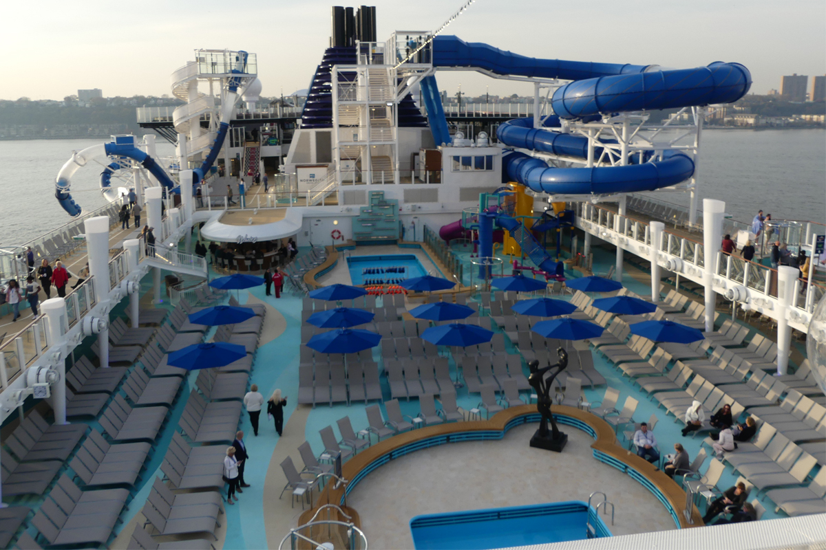 Norwegian Encore's pool deck with waterslides and children's waterpark.
